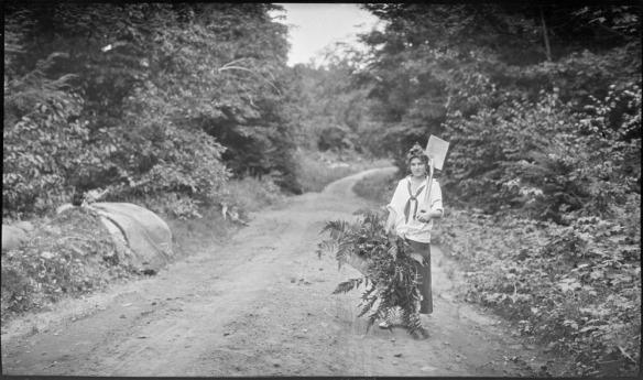 Photographie en noir et blanc d'une femme debout sur une route de terre portant un panier rempli de fougères et une pelle sur l'épaule gauche.