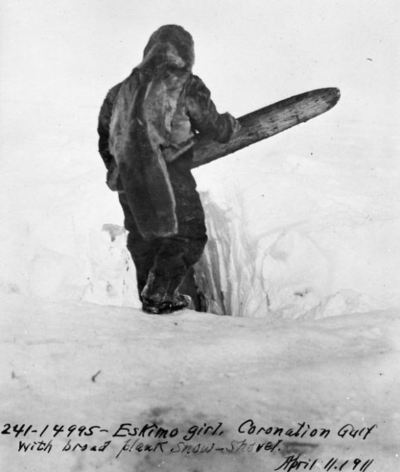 Photographie en noir et blanc d'une femme utilisant une pelle à neige traditionnelle faite d'une large planche de bois pour construire un iglou.