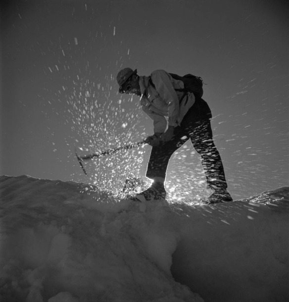 Photographie en noir et blanc d'un homme penché en avant et cassant la glace avec un piolet.
