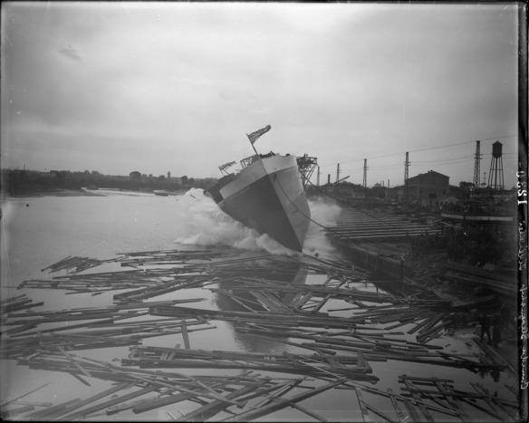 Photo noir et blanc de la mise à l'eau d'un navire, parmi les rondins et d'autres débris flottant sur l'eau.