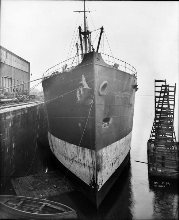 Photo noir et blanc d'un grand navire. On aperçoit un renfoncement sur le côté de la coque qui fait face à l'eau.
