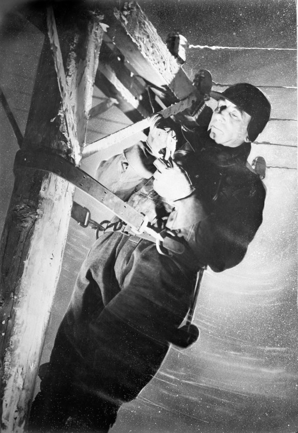 Photo noir et blanc d'un homme accroché à un poteau de téléphone, réparant des câbles sous le vent et la neige. Il porte un manteau d'hiver, des gants et un chapeau.