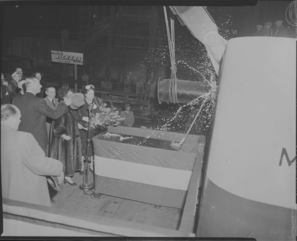 Photo noir et blanc où des hommes et des femmes regardent une bouteille de champagne se briser sur la coque d'un énorme navire. Un homme place son chapeau devant le visage d'une femme vêtue d'un manteau de fourrure.