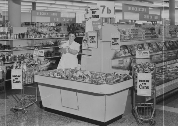 Photo noir et blanc prise dans une épicerie, où une femme vêtue d'une robe blanche verse le liquide provenant d'une canette dans un verre. Elle est debout derrière un présentoir rempli de boissons en canettes, flanqué de deux paniers d'épiceries couverts d'affiches sur lesquelles on peut lire « Now in Cans » (Maintenant en canette).