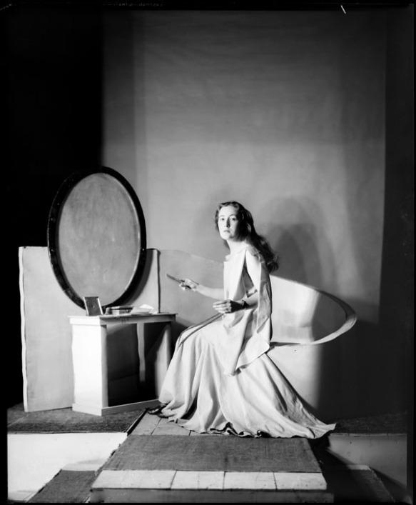Photographie noir et blanc d'une femme aux longs cheveux noirs vêtue d'une robe blanche flottante. La femme est assise devant un miroir ovale et regarde en direction de l'appareil photo.