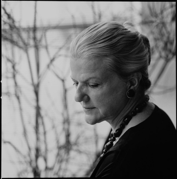 Photographie noir et blanc d'une femme de profil aux cheveux gris portant un collier foncé.