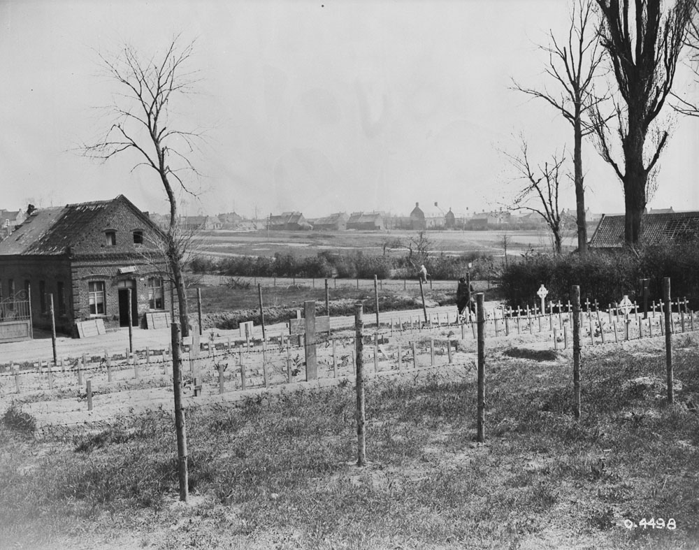 Photo noir et blanc d'un cimetière derrière une clôture, avec quelques petits arbres sans feuilles, près de Cambrai, en France. À l'arrière-plan, on aperçoit une maison et une ferme.