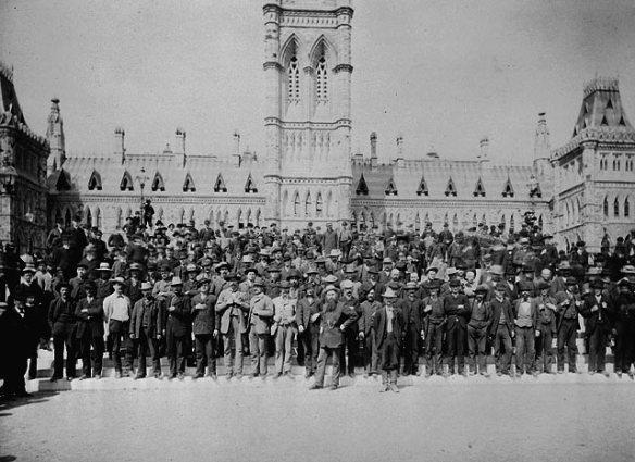 Photo noir et blanc d'un grand groupe d'hommes posant devant les édifices du Parlement.