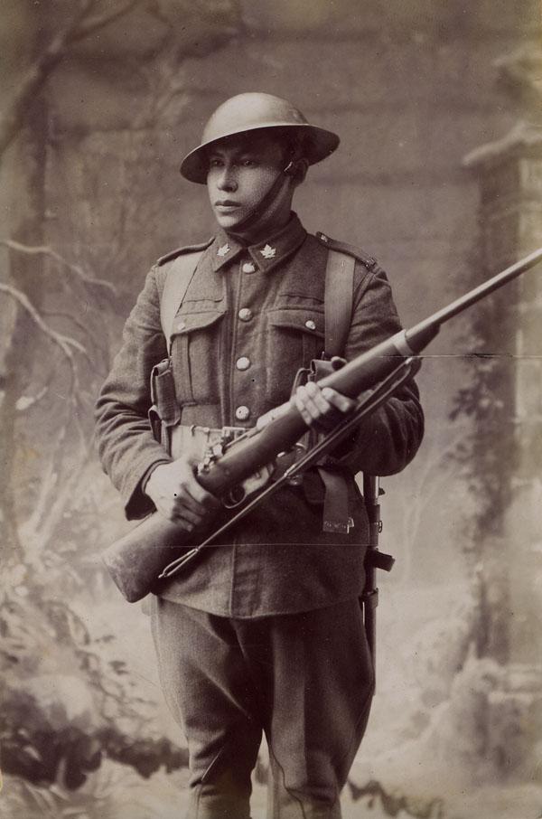 Portrait studio en noir et blanc d'un soldat de la Première Guerre mondiale, vêtu d'un uniforme, qui tient une carabine.