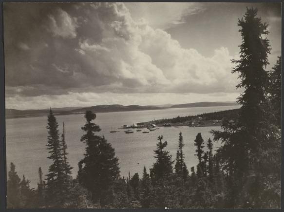 Photo noir et blanc de bateaux dans une baie. On voit des arbres à l'avant-plan.