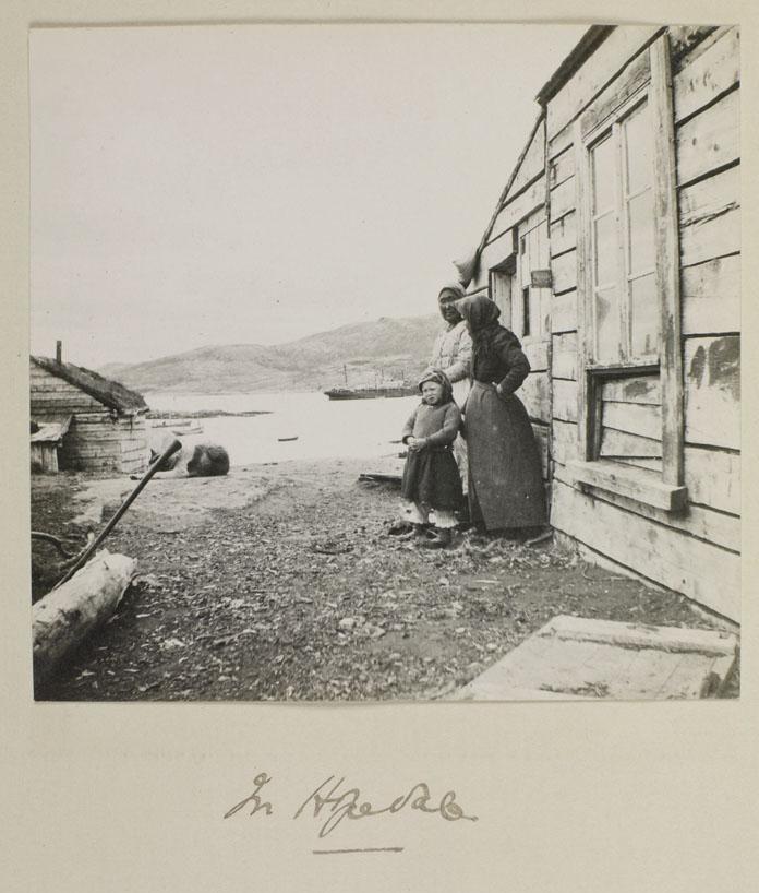 Photo noir et blanc de deux femmes et d'un enfant inuits, debout à côté d'une maison en bois.