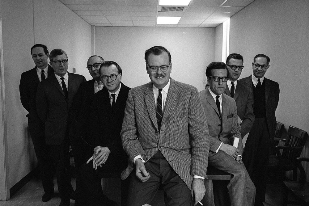 Photo noir et blanc de huit hommes en complets, souriant devant l'objectif, dans une salle de conférence aux murs clairs.