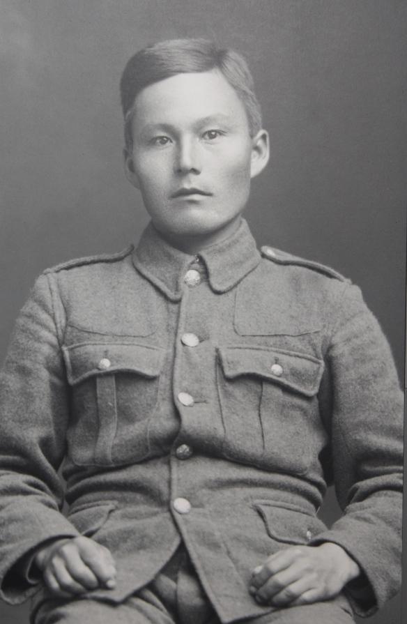 Photo noir et blanc d'un jeune homme inuit vêtu d'un uniforme militaire, qui regarde l'objectif.