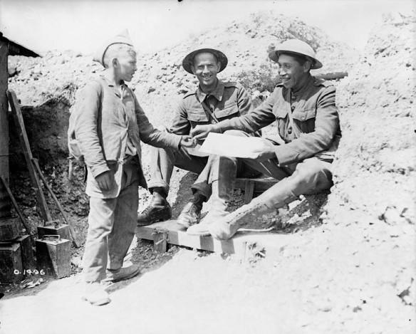 Photo noir et blanc de deux militaires portant un uniforme de la Première Guerre mondiale. Assis, sourire aux lèvres, ils achètent un journal d'un jeune garçon. Le militaire à droite prend le journal d'une main et donne l'argent au garçon de l'autre.