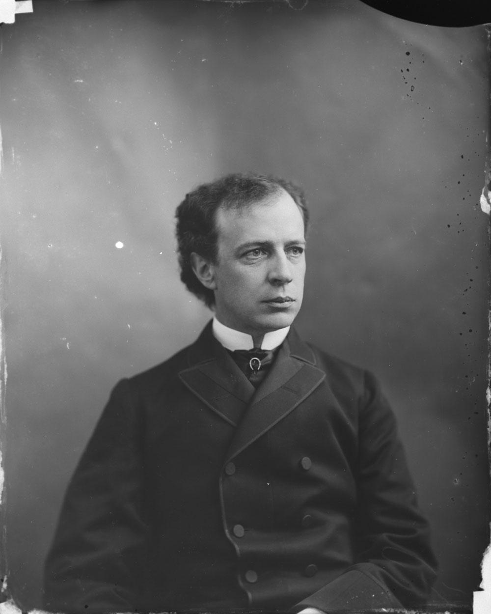 Photo noir et blanc d'un homme assis, vêtu d'un complet.
