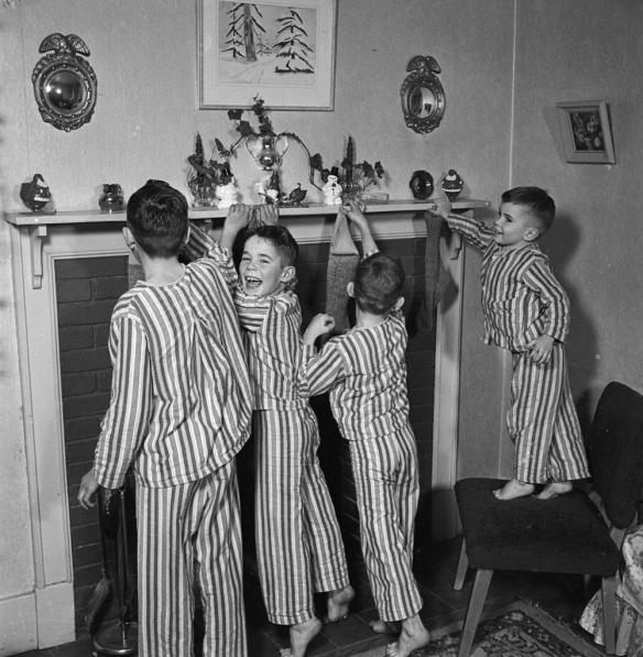Photo de quatre garçons vêtus du même pyjama rayé accrochant leurs bas de Noël sur le manteau de la cheminée.