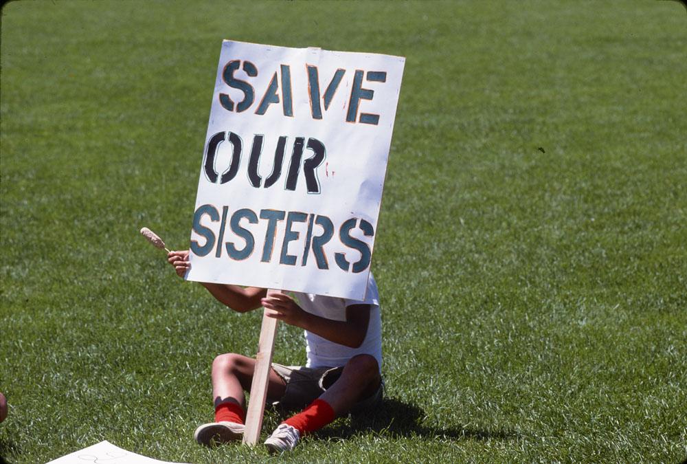 Photographie couleur d'une personne assise sur une pelouse verte derrière une pancarte où sont écrits les mots « Save our sisters », ou « Sauvez nos sœurs ».