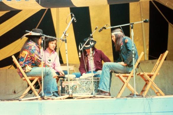 Photographie couleur montrant quatre hommes assis sur des chaises de bois, entourés de microphones et se faisant face. Ils chantent et jouent du tambour.