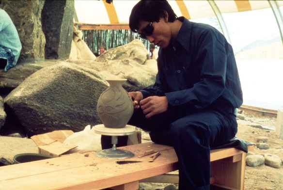 Photographie d'un homme portant des vêtements bleu foncé et des lunettes de soleil. Il est assis sur un banc de bois et sculpte un vase.