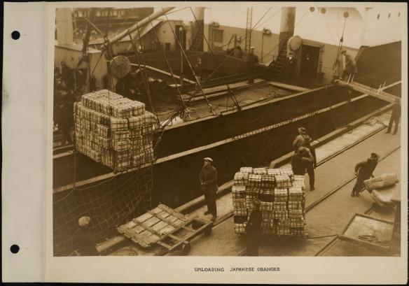 Des travailleurs portuaires déchargent des cageots de mandarines d'un navire à l'aide de grues et de chariots.