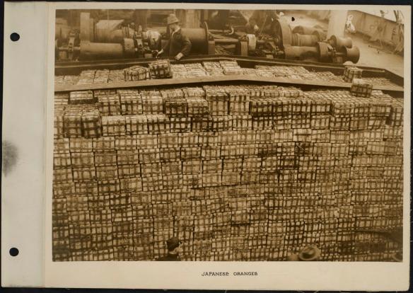 Photo de travailleurs avec des centaines de cageots de mandarines sur le pont d'un navire.