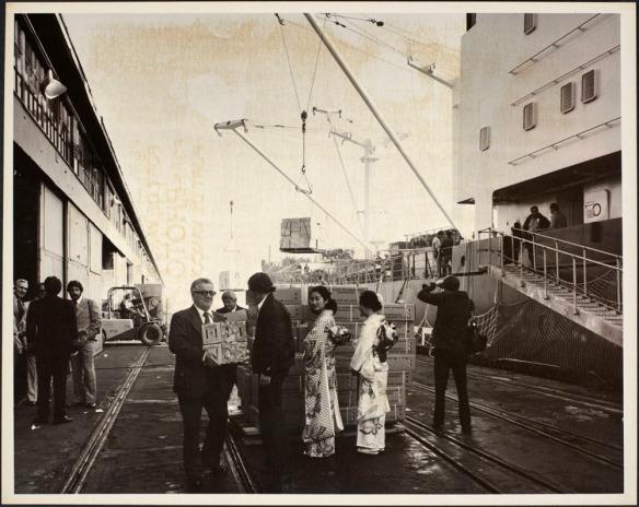 Photo montrant les dirigeants d'un port tenant des cageots de mandarines, deux femmes japonaises en costume traditionnel à côté d'une palette de cageots de mandarines ainsi que d'autres personnes et de l'équipement sur la jetée située à côté d'un navire.