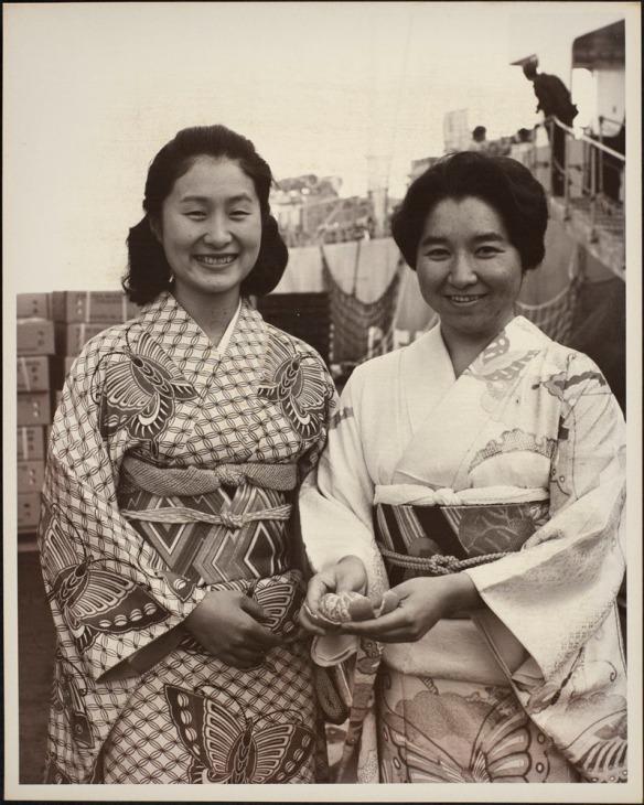 Photo de deux femmes japonaises en costume traditionnel. L'une d'elles tient une mandarine pelée. On aperçoit des cageots de mandarines et un navire à l'arrière-plan.