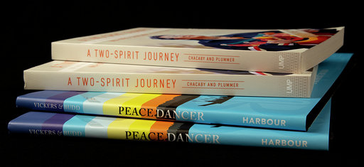 Photographie couleur de quatre livres placés dans une pile