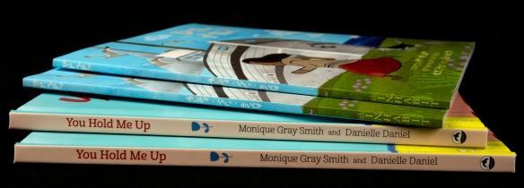 Photographie couleur de quatre livres placés dans une pile.