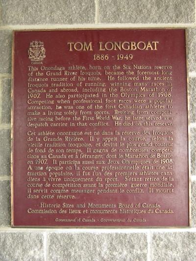 Plaque rouge rectangulaire arborant un texte doré, surmonté de l'emblème du Canada et de l'inscription « Tom Longboat 1886-1949 ».