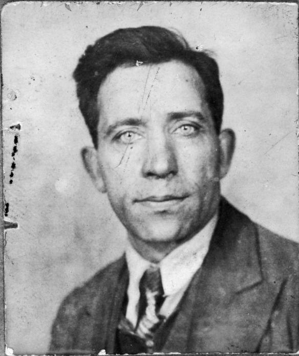 Photographie noir et blanc d'un homme en complet-cravate fixant l'appareil photo.