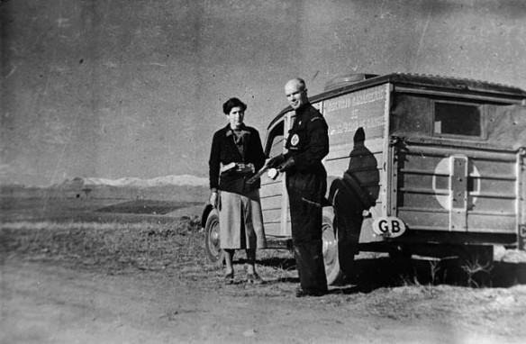 Photographie noir et blanc d'un homme et d'une femme debout devant une camionnette dont l'arrière est marqué d'une marqué d'une croix.