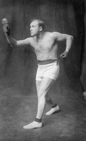 Photo noir et blanc d'un homme portant des gants, un short et des chaussures de boxe.