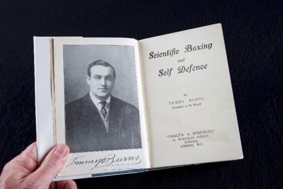 Photo noir et blanc d'une main tenant un livre ouvert à la page de titre.