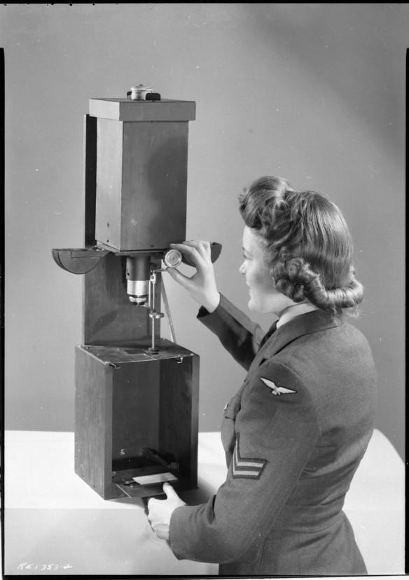 Photo noir et blanc d'une femme en uniforme militaire manipulant un agrandisseur.