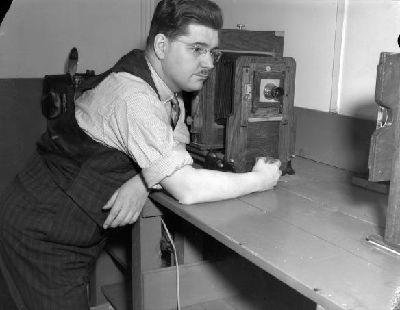 Photo noir et blanc d'un homme appuyé sur un bureau à côté d'un agrandisseur.