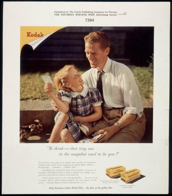 Un homme en chemise et cravate est assis auprès d'une fillette en robe à carreaux; il sourit en regardant une photo. Le nom de la marque (Kodak) figure dans le coin supérieur gauche de l'image.