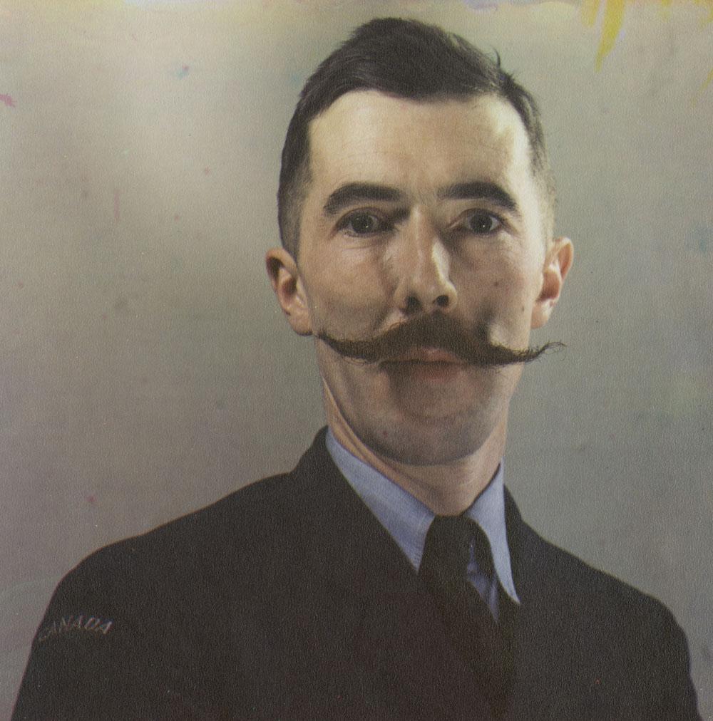 Autoportrait couleur de Brodie Macpherson en uniforme militaire arborant une moustache en guidon. Le sujet est représenté jusqu'à la poitrine devant un arrière-plan vierge.