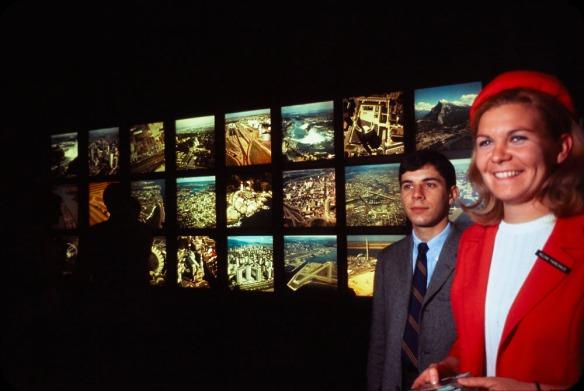 On aperçoit au premier plan une représentante de Kodak et un homme. On voit derrière eux des diapositives couleur rétroéclairées montrant des vues aériennes.