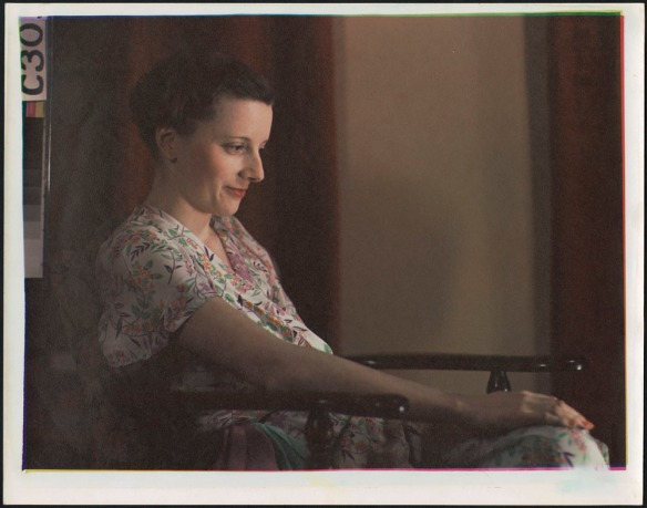 Portrait couleur d'une femme portant une robe fleurie, le visage éclairé, assise dans une chaise à appuie-bras en bois.