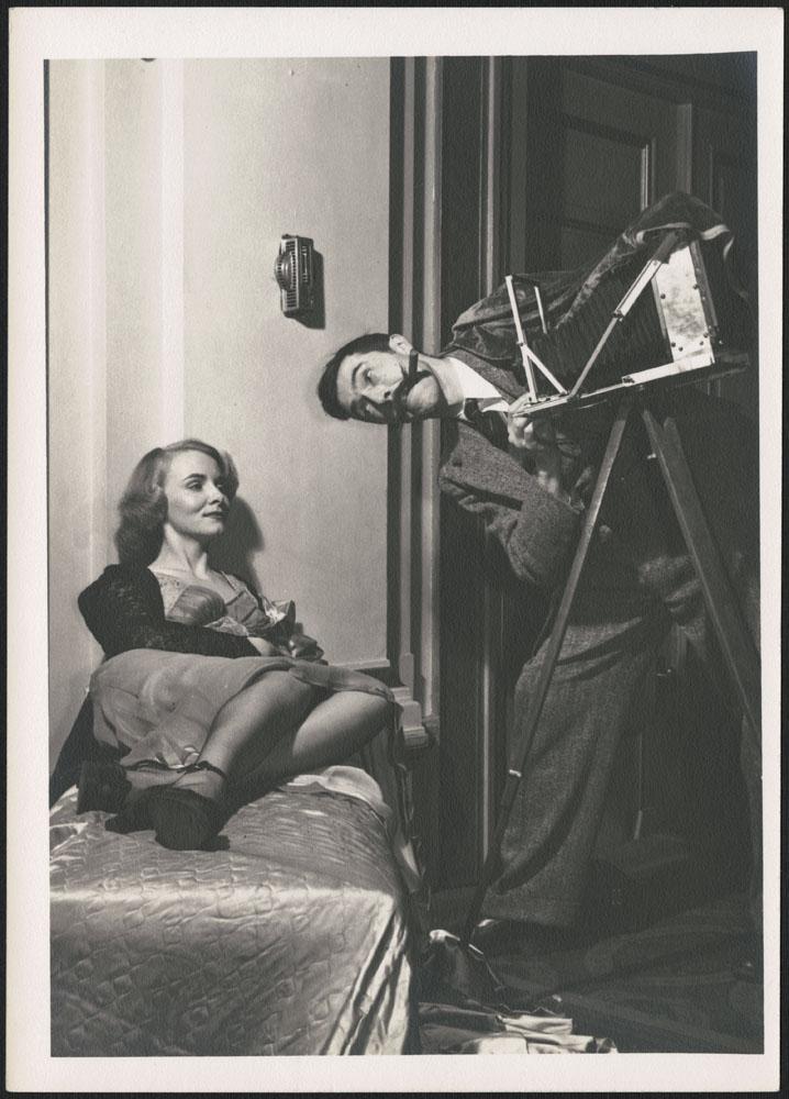 Photographie noir et blanc de Brodie Macpherson faisant semblant de prendre en photo Miss 1948, Lialla Raymes, alors qu'elle est allongée.
