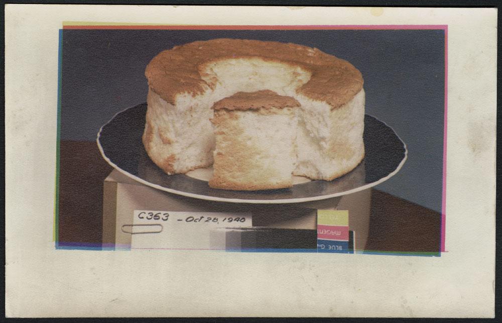 Photo d'un gâteau rond coupé sur une assiette noire, placé sur une boîte portant la matrice d'impression et le numéro de créateur C363.