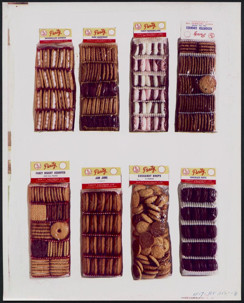 Photo publicitaire montrant huit variétés de biscuits et de petits gâteaux Purity dans des sacs transparents sur fond blanc.