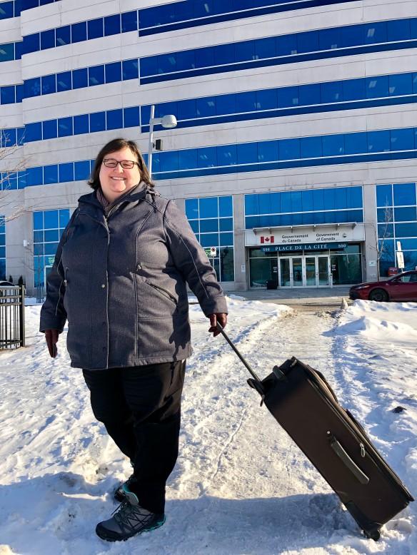 Photo couleur d'une femme avec une valise, devant un édifice.