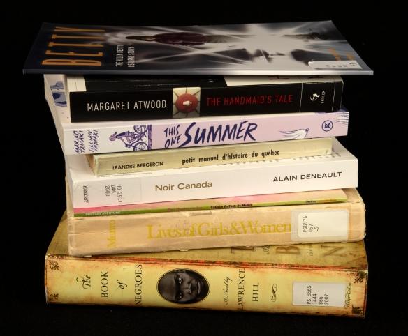 Photographie couleur montrant le dos de livres empilés sur fond noir.
