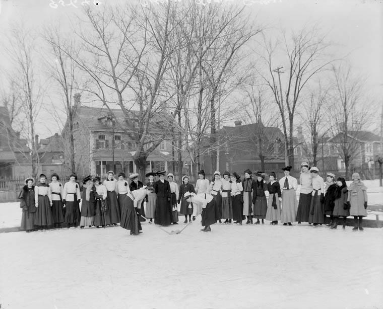 : Photographie noir et blanc, prise à l'extérieur, montrant des femmes en jupe longue.