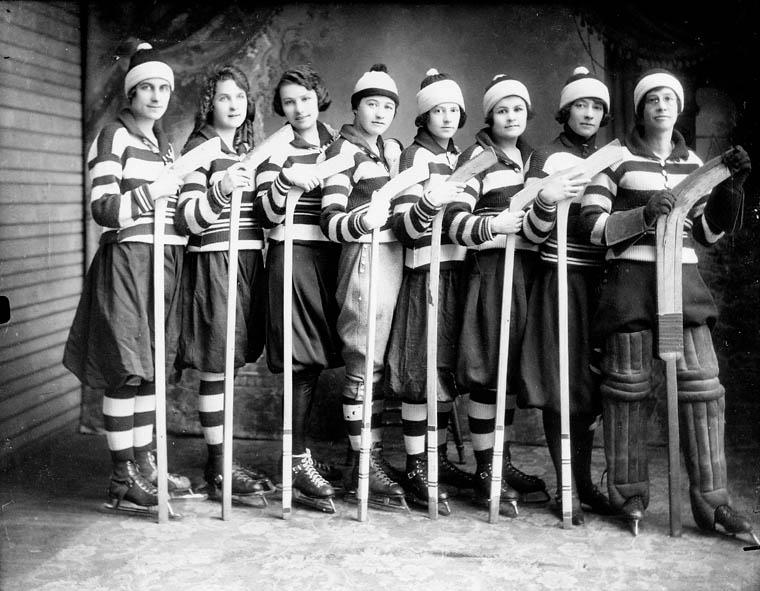 Photographie noir et blanc d'une équipe de hockey féminin. Les huit joueuses, en uniforme, sont placées côte à côte et tiennent leur bâton la palette vers le haut.