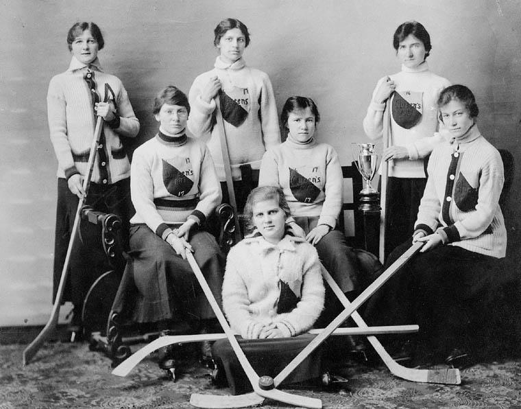 Photographie noir et blanc d'une équipe de hockey féminin. Les joueuses portent des chandails d'équipe et tiennent chacune un bâton.