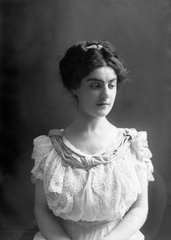 Photo noir et blanc d'une jeune femme en robe de dentelle blanche, face à l'objectif.