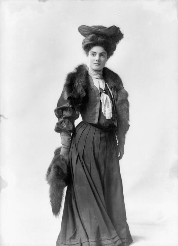 Photo noir et blanc d'une femme debout face à l'objectif, portant une robe de couleur sombre, un chapeau de fantaisie et une étole en fourrure.